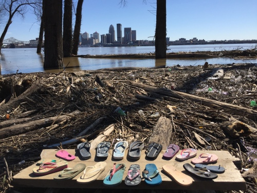 Improvised found flip-flop piece on wood panel on a high Ohio River with Louisville in the distance.  2018