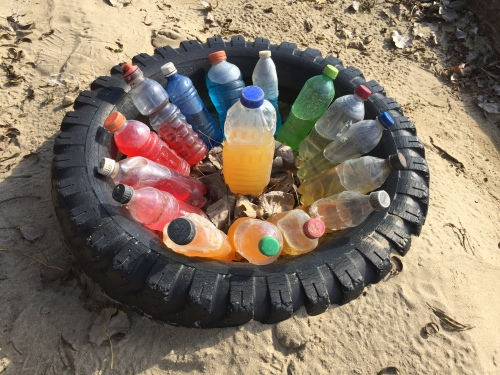 Sunken tire and found soft drink bottle with contents piece